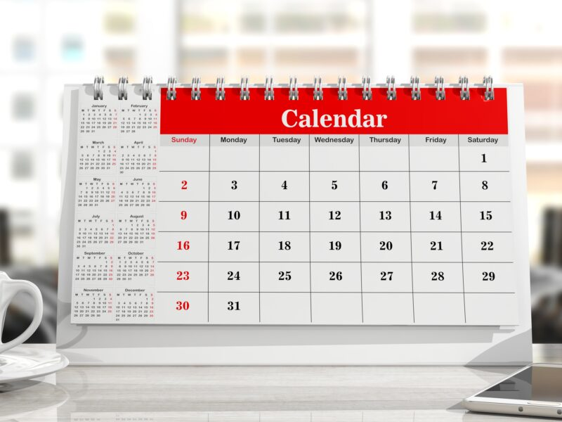 Desk calendar, a smartphone and a cup of coffee on an office background. 3d illustration
