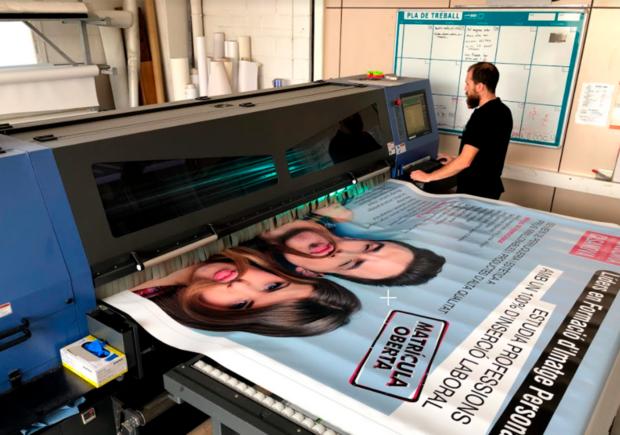 hombre trabajando con impresora material publicitario para eventos graficser