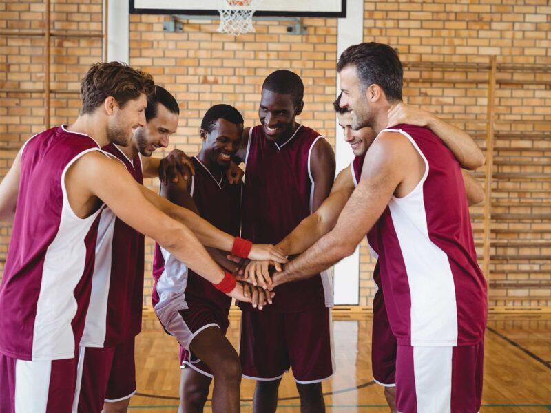 equipo de básquet con manos juntas